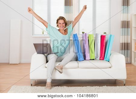Woman On Sofa With Laptop And Shopping Bags