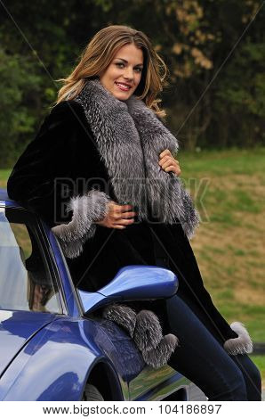Wealthy Woman In Fur Coat Leaning On A Sports Car