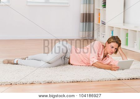 Woman With Digital Tablet Lying On Carpet