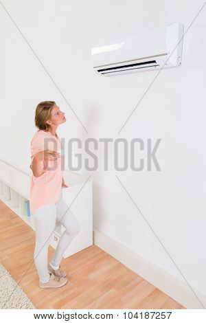 Woman Operating Air Conditioner