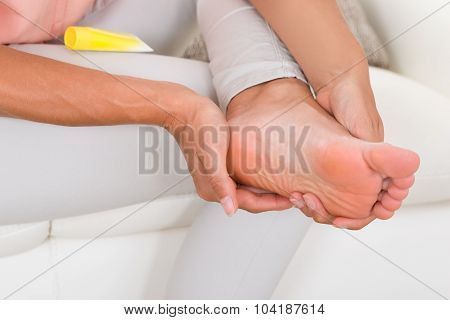 Woman's Hand Applying Cream On Foot