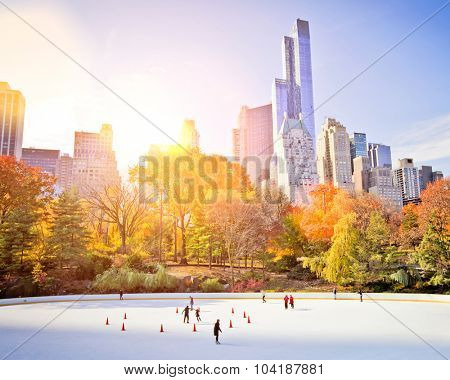 Ice skaters having fun in New York Central Park in fall with sun flare