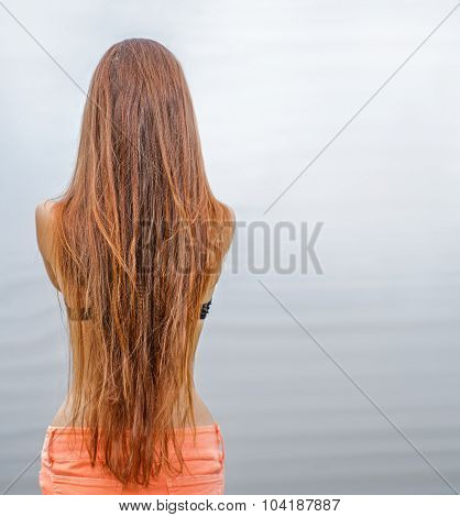 Rear view of long haired redhead woman posing against sea water, a lot of space for text