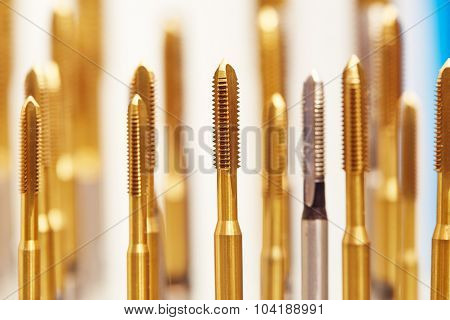 heap of finished metal thread tap tools with protective coating, Shallow DOF
