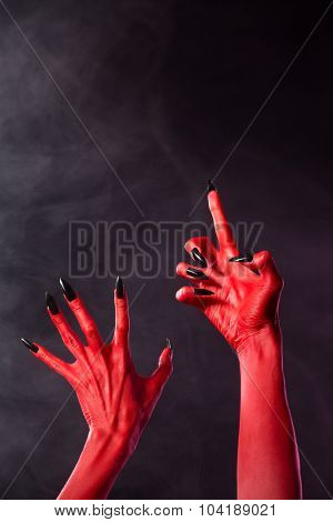 Scary red devil hands with black nails on smoky background with copy-space