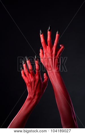 Red devil hands with black nails reaching out, Halloween theme