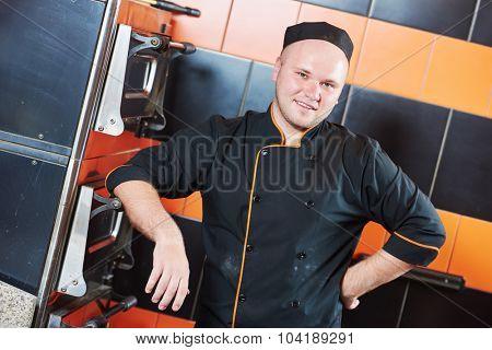 portrait of chef baker cook in uniform at restaurant kitchen near pizza oven
