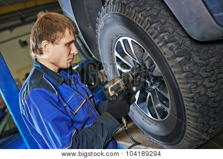 car mechanic screwing or unscrewing car wheel of lifted automobile by pneumatic wrench at repair service station. Focus on hand and hands.