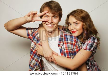 Couple in love.Young woman and man wearing casual wear over grey background.