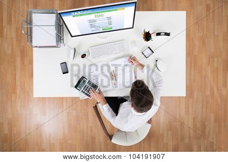 Businessman Calculating Tax In Front Of Computer