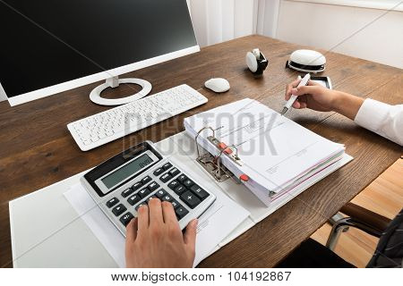 Businessman Checking Invoice With Calculator