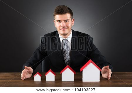 Businessman Protecting House Models At Desk