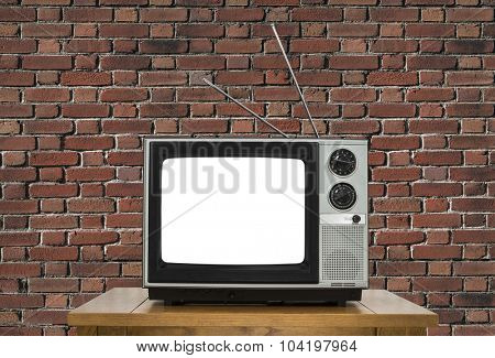Old analogue television with cut out screen and brick wall.