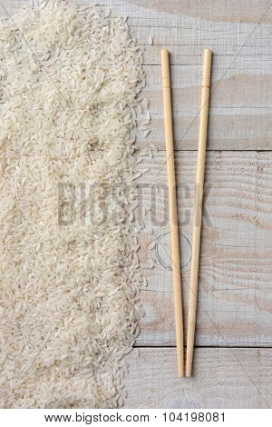 High angle view of chop sticks laying next to a pile of white rice on a rustic wood table.