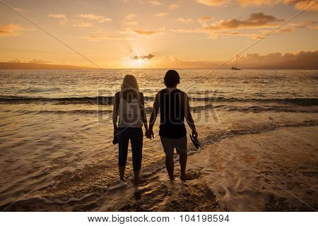 Couple in love walking along the beach barefoot together at sunset. Wide angle photo with lots of copy space