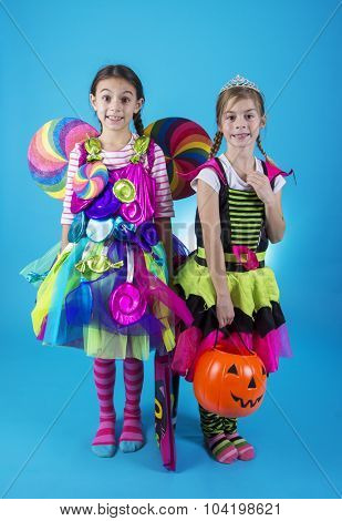 Cute little girls in Halloween costumes ready to go trick or treating