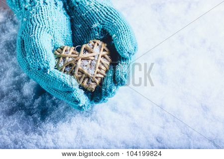 Female hands in light teal knitted mittens with entwined beige flaxen heart on a white snow winter background. Love and St. Valentines Day cozy concept.