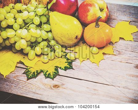 Autumn background with colorful leaves and pumpkins on rustic wooden board. Fall fruit and vegetables on wood. Thanksgiving dinner and Halloween holidays concept. Harvest rural fall season. Copyspace.