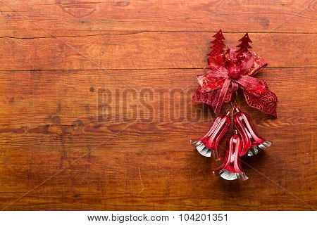 Bells and red loop on wooden background.