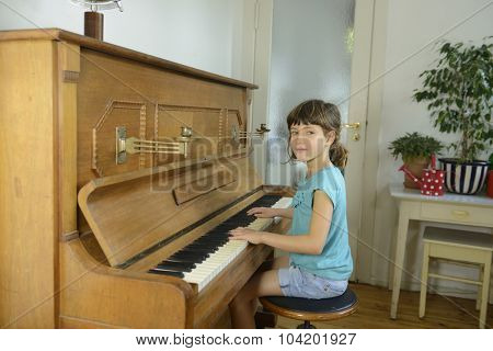 Child learning to play piano at home