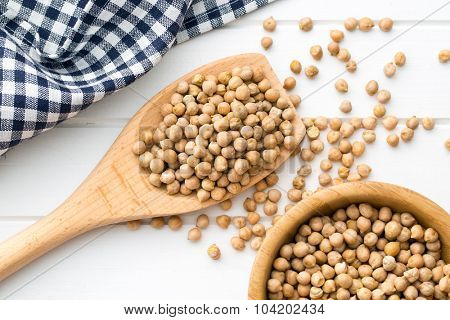 uncooked chickpeas on a wooden spoon