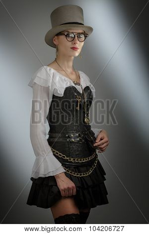 Girl In A Stylized Steampunk Costume Posing On A Dark Background.