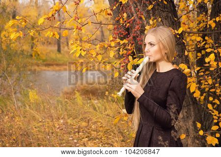 Beautiful Young Blonde Woman Playing Flute Recorder In Autumn Forest