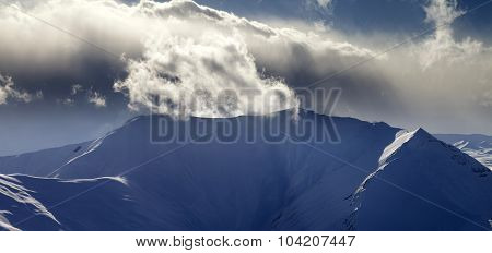 Panoramic View Of Mountains In Sunset With Sunlit Clouds