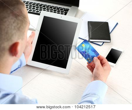 Man holding credit card and tablet on workplace background