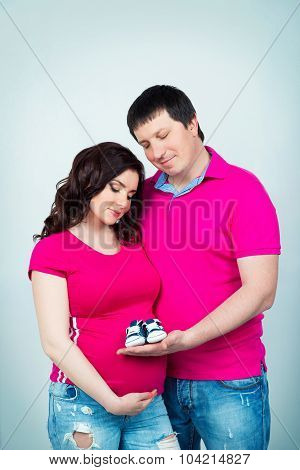Young Beautiful Pregnant Couple In Crimson Shirt With Baby Booties In Hands