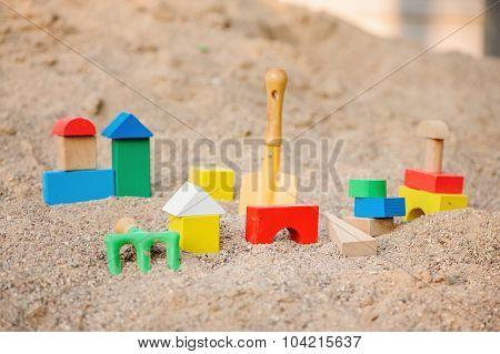 toy houses and trucks made of wooden bricks in sandbox