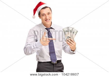 Young businessman with Santa hat holding bunch of money and pointing with his hand towards them isolated on white background
