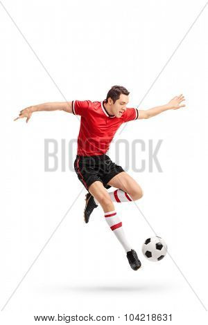 Full length portrait of a young football player in red jersey kicking a ball in mid-air isolated on white background