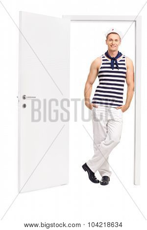 Full length portrait of a young male sailor leaning against the frame of an open door isolated on white background