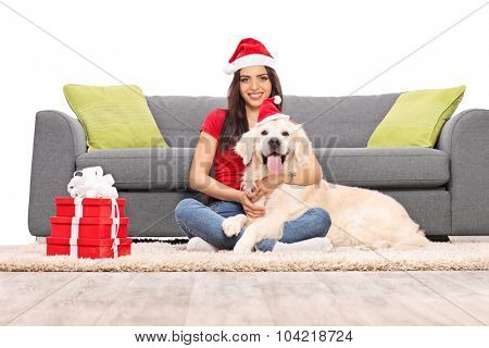 Young woman with Santa hat sitting on the floor in front of a gray couch and hugging her pet dog isolated on white background
