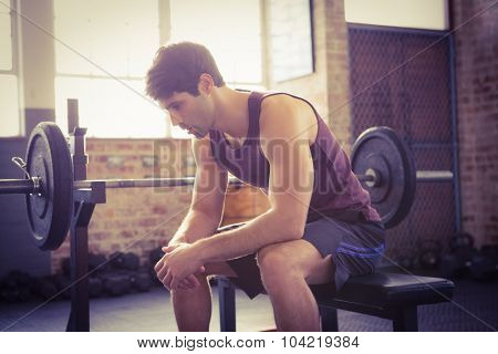 Focused man sitting on the bench at the gym