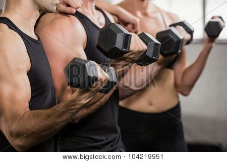 Midsection of people at gym lifting dumbbell