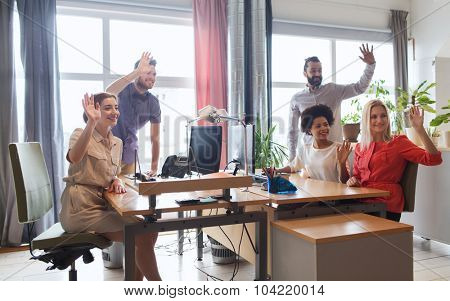 business, startup and office concept - happy creative team waving hands in office