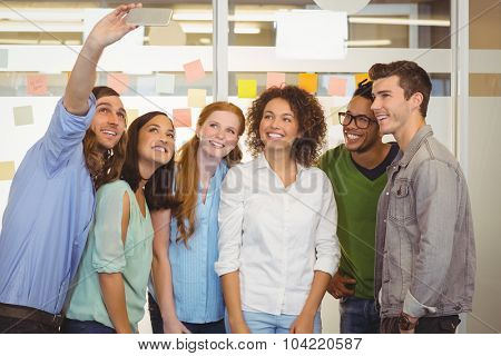 Smiling business people taking selfie in office
