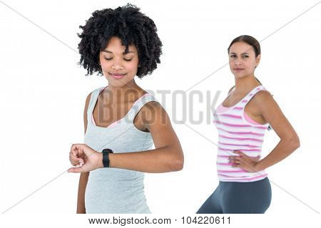 Fit woman checking wristwatch while female friend exercising against white background