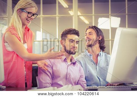 Happy businesswoman with male colleagues in creative office