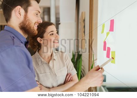 business, startup, planning, management and people concept - happy creative team with stickers on office glass board