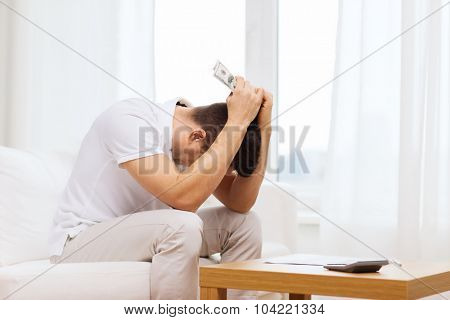 business, savings, financial crisis and people concept - man with money and calculator at home