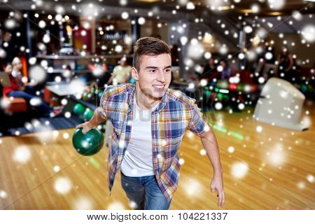 people, leisure, sport and entertainment concept - happy young man throwing ball in bowling club at winter season