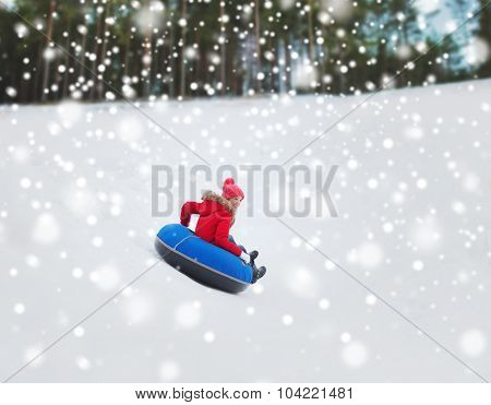 winter, leisure, sport, and people concept - happy teenage girl or woman sliding down on snow tube