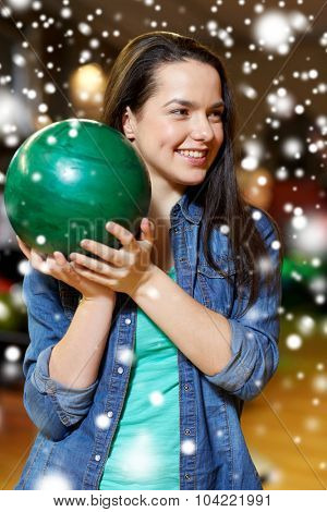 people, leisure, sport and entertainment concept - happy young woman holding ball in bowling club at winter season