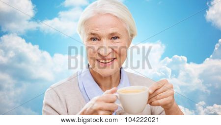 age, drink and people concept - happy smiling senior woman with cup of coffee over blue sky and clouds background