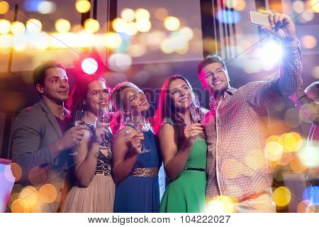 party, holidays, technology, nightlife and people concept - smiling friends with glasses of non-alcoholic champagne and smartphone taking selfie in club