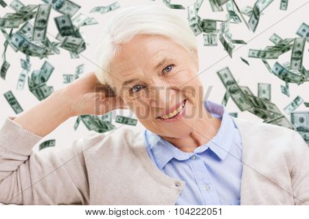 age, pension, finances, insurance and people concept - happy smiling senior woman over dollar money rain on background
