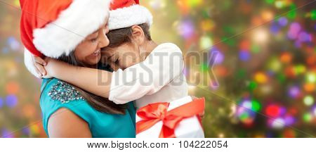 christmas, family, childhood and people concept - happy mother and little girl in santa hats cuddling over holidays lights background